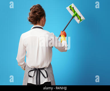 Seen from behind young cleaning woman in apron using mop on blue background. Cleaning experts always know how best to clean up your home or office - Stock Photo