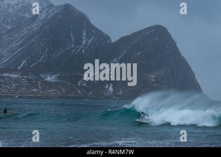 Distant view shot of two surfers in sea, Unstad beach, Vestvagoya, Lofoten Islands, Norway - Stock Photo