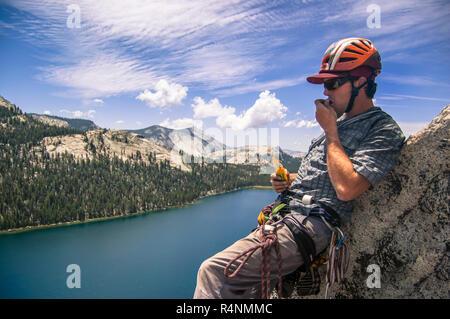 View of single adventurous man eating snack while rock climbing above lake in Tuolumne Meadows, Yosemite National Park, California, USA - Stock Photo