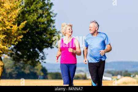 Senior woman and man running doing fitness exercises - Stock Photo