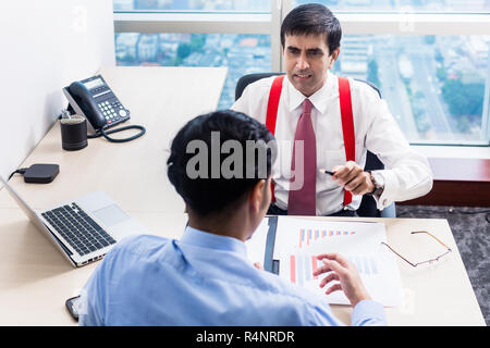 Supervisor talks to subordinate professional in office building - Stock Photo