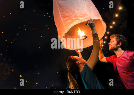 Man and woman holding paper lantern during Yi Peng festival, Chiang Mai, Thailand - Stock Photo