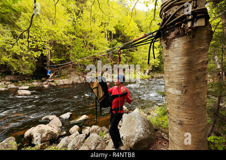 Climber traversing across the Au Sable River to access the climbing a route on Moss Cliff above Wilmington Notch, Adirondack Mountains, New York State, USA - Stock Photo