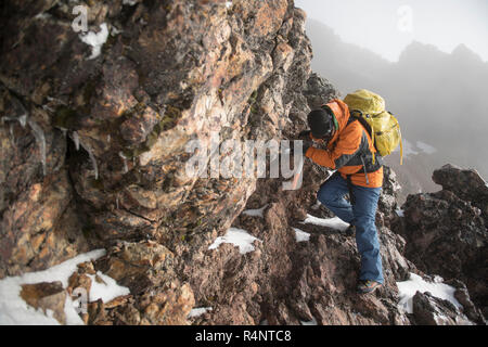One man climbs trough a rocky section using a piolet, or ice axe, on his ascent to the Iztaccihuatl volcanoe at the Izta-Popo Zoquiapan National Park in Puebla, Mexico - Stock Photo