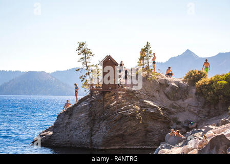 Swimmers wait on a rock outcrop surrounded by a big blue lake on sunny summer day, Crater Lake, Oregon, USA - Stock Photo