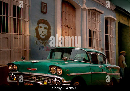 Vintage car and graffiti of Che Guevara in street, Trinidad, SanctiSpritusProvince, Cuba - Stock Photo