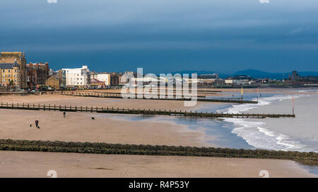Portobello, Edinburgh, Scotland, United Kingdom, 28th November 2018. UK Weather: Dark storm clouds gather over people walking dogs on the sandy beach at Portobello as Storm Diana approaches. The beach has wooden groynes to protect the shore - Stock Photo
