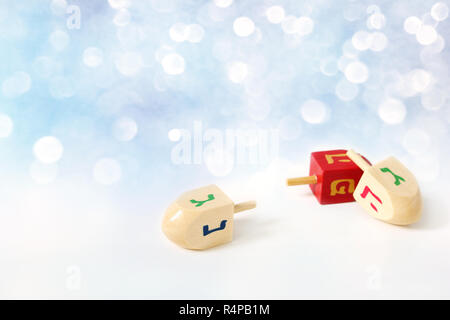 Happy Hanukkah greeting card, invitation Traditional Jewish Festival of lights holiday symbols. Wooden dreidel toys on white table. Festive glittering - Stock Photo