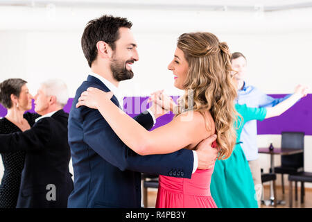 Young and senior couples getting dance lessons - Stock Photo