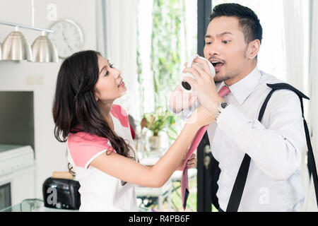 Asian man being late for office hurrying breakfast - Stock Photo
