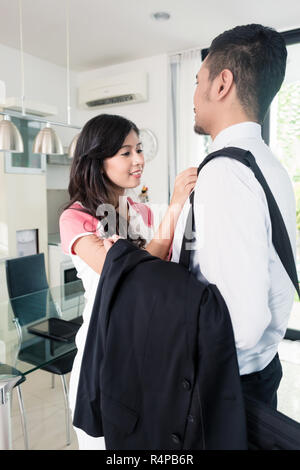 Wife helping her man going to office for work - Stock Photo