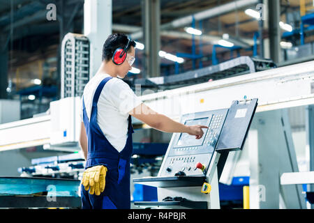 Worker entering data in CNC machine at factory
