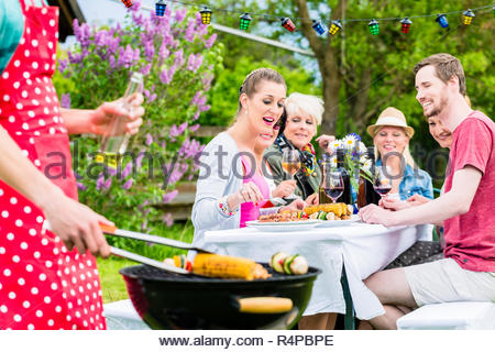 Man grilling meat and vegetables on garden party - Stock Photo