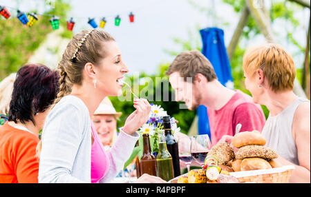 Woman eating grilled sausage on bbq party - Stock Photo