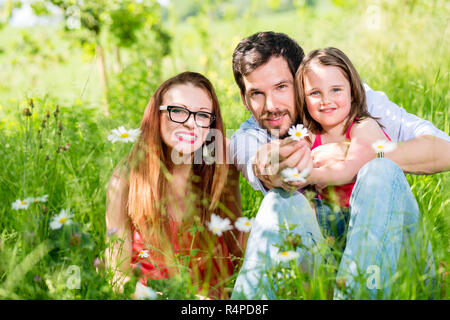 Family sitting on meadow giving their kid protection - Stock Photo