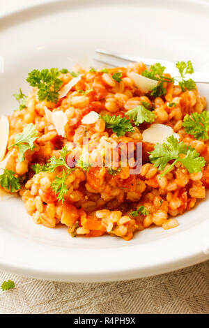 Pearl barley and tomato stew on white platter - Stock Photo
