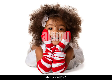 Portrait of a preschool cafrican-american girl laying down. Studio shot. Isolated on white background - Stock Photo