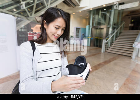 Woman using VR device in museum - Stock Photo