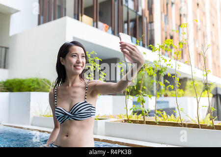 Woman taking selfie by mobile phone in jacuzzi spa - Stock Photo