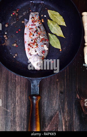 Fish carp in spices on a black cast-iron frying pan - Stock Photo