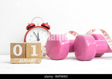 New Year's resolutions to work out, healthy lifestyle and diet concept. Pink dumbbells, alarm clock, and measuring tape with block calendar for Januar - Stock Photo
