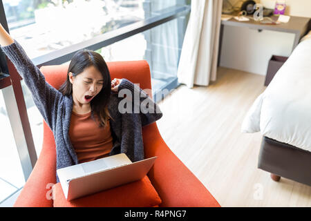 Woman feeling tired when working on notebook computer at home - Stock Photo