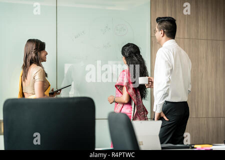 Three Indian colleagues writing ideas during brainstorming - Stock Photo