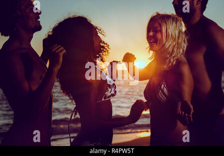 Men and women having party at ocean beach dancing in the sunset - Stock Photo