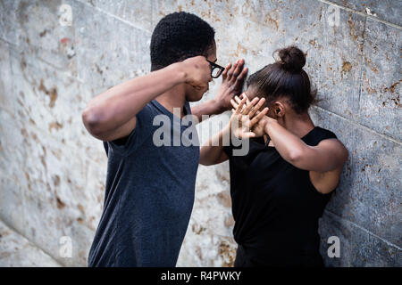 Violent young man threatening his girlfriend with his fist outdoors - Stock Photo