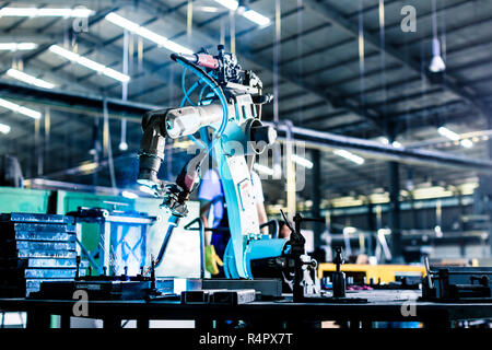Welding robot in production plant or factory - Stock Photo