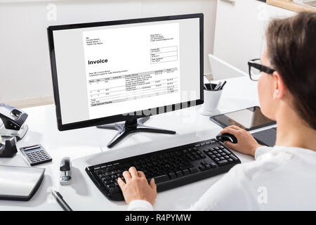 Businesswoman Calculating Invoice On Computer - Stock Photo