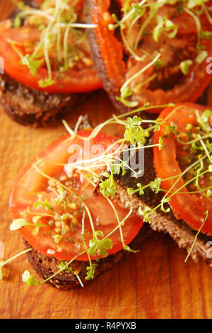 Sandwiches with hemp butter and tomatoes on table - Stock Photo