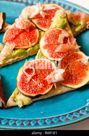 Pizza  with fresh figs, avocados and maple syrup on platter - Stock Photo