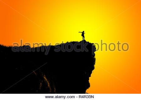 Silhouette woman on peak mountain - Stock Photo