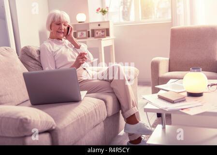 Nice elderly woman having a pleasant conversation - Stock Photo