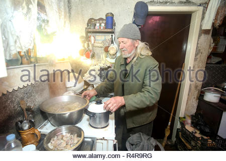 Old man boiling meat - Stock Photo