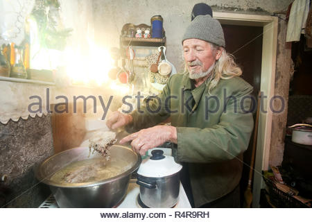 Old man boiling pork - Stock Photo
