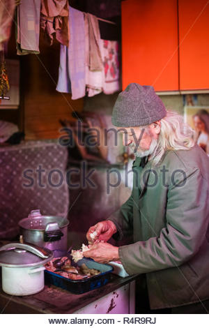 Old man cooking meat - Stock Photo