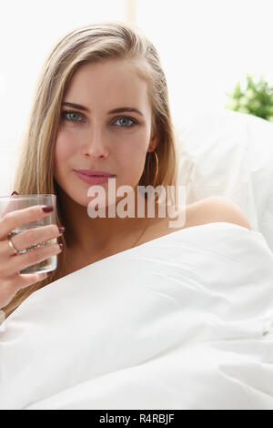 blond woman hold glass of water in arm early morning stay in bed - Stock Photo