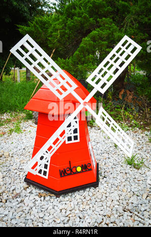 colorful red windmill wind turbine in the park garden - landscape windmill nature hill background - Stock Photo