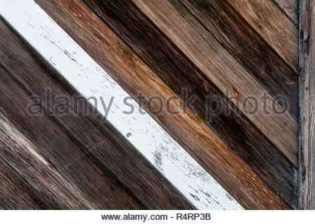 Closeup on diagonal wood boards fence with various shades of brown and one central, white board- texture and background - Stock Photo