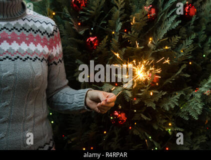 Woman in knitted sweater holding sparklers before christmas tree - Stock Photo