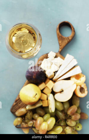 Glass of white wine with appetizers wine. Fruit and cheese on wooden board on stone background. Wine appetizers - Stock Photo