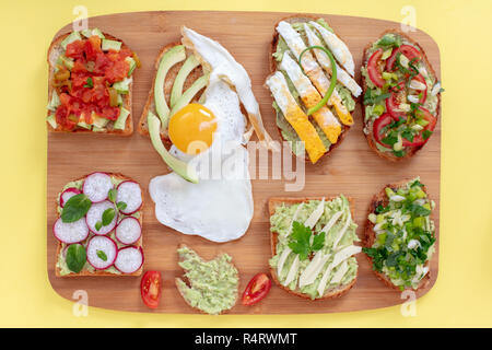 Variation of  healthy breakfast sandwiches  on toasted breads with avocado and different ingredients on wooden background. Flat lay top view. - Stock Photo