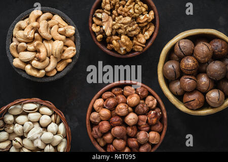 Various nuts in bowls on black background. Hazelnut, cashew nuts, pistachios, macadamia and walnuts. Top view - Stock Photo