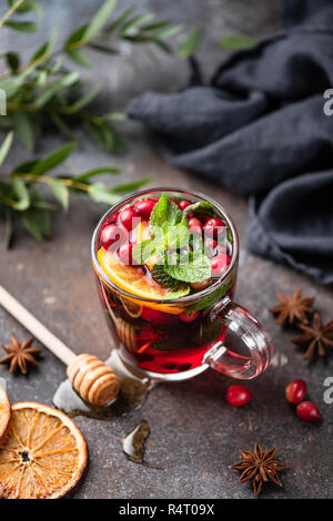 Hot spicy cranberry mulled wine or cranberry tea in glass cup decorated with orange peel and mint leaf - Stock Photo