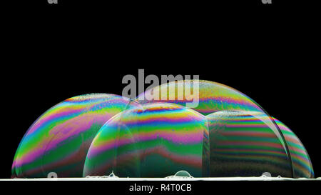 iridescence on the surface of some soap bubbles illuminated from below - Stock Photo