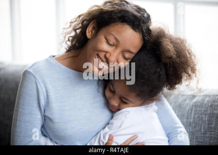 Loving African American mother embracing with daughter - Stock Photo
