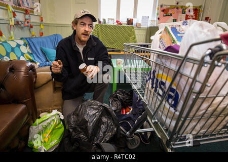 Tony Lee, a needy family man, is looked after by volunteer helpers at the Arnold Food Bank Daybrook Baptist Church's food store in Nottingham and provided with donated food for his family. - Stock Photo