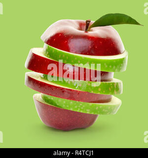Mixed green and red apple slices piled up and isolated on green background. - Stock Photo